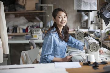Fashion designer working with sewing machine in studio