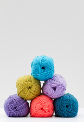 Balls of colourful wool in a pile of six and isolated on a white background.