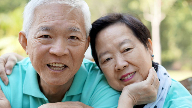 close up potrait of smiling Asian senior couple on bright green