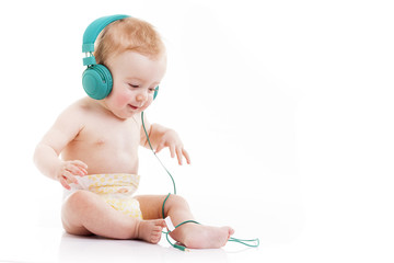 Happy baby with headphones listening to music on white backgroun