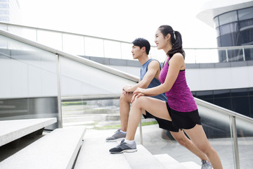 Young couple stretching legs on stairs