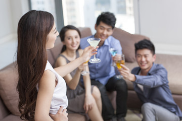 Happy young friends drinking cocktail in living room