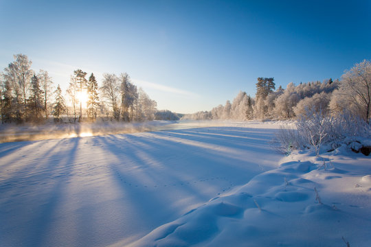 Winter landscape with the river at dawn