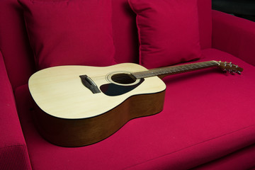 a guitar put on red sofa