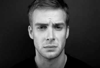 Black and white portrait photo of young man with sad look in v n