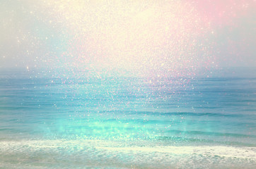 background of blurred beach and sea waves with bokeh lights, vintage filter.