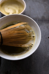 Close up of the bowl of fresh matcha tea with bamboo whisk