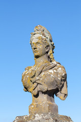 Od weathered stone bust of Marianne, a symbol of the French Republic and France, allegorical of Freedom and Reason, covered in colourful lichen against a clear blue sky with copy space