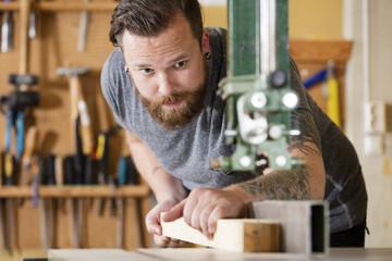 Craftsman using bandsaw for splitting wood plank in workshop