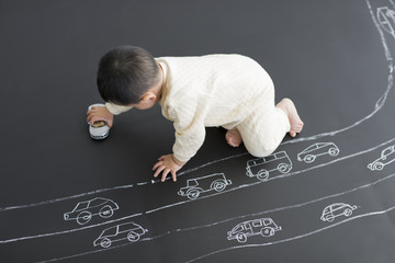 Cute baby playing with toy car on drawing board