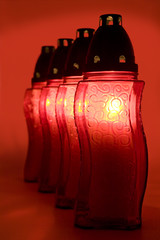 An illuminated votive candles standing in a row