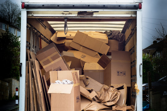 Removal van with untidy boxes dumped inside. A removal lorry is filled with carelessly thrown boxes