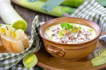 Deftige Hackfleisch-Lauch-Suppe in der handgetöpferten Suppenschale mit Butter-Baguette auf Holztisch serviert