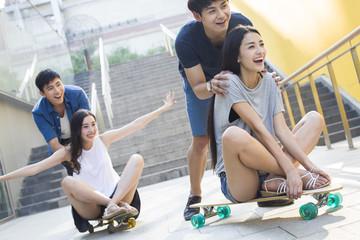 Young men pushing girlfriends on skateboards