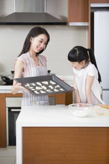 Happy mother and daughter baking cookies