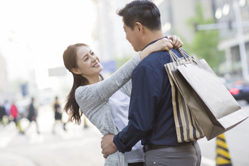 Happy couple looking at each other on street while holding bags