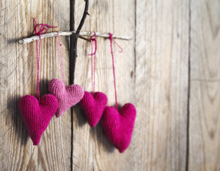 Crochet pink hearts on wooden background. Toned image