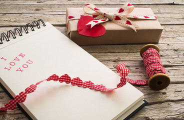 gift, ribbon and notebook with I love you