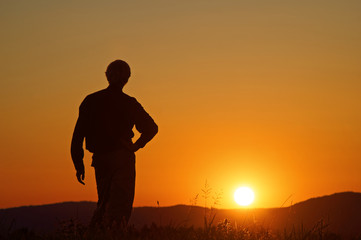 Man watching the sunset on a grassy horizon. Silhouette. Wooded mountains in the background.