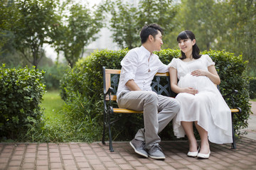 Pregnant woman and her husband sitting on bench