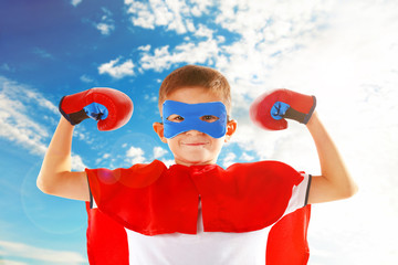 Boy dressed as superhero with boxing gloves on sky background