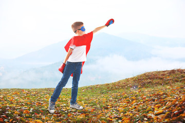 Boy dressed as superhero with boxing gloves on mountains background