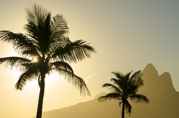 Sunset in Rio de Janeiro Ipanema Beach Brazil with Two Brothers Dois Irmaos Mountain and palm tree silhouettes