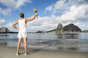 Young athletic man standing with sport torch against Rio de Janeiro Brazil skyline at Botafogo Bay with Sugarloaf Mountain