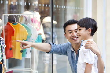 Smiling father showing clothes to son in a shopping mall