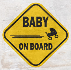 funny baby on board sign on wood grain texture
