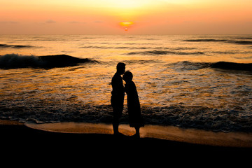 silhouette of  couple about to kiss on beach