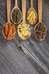 A set of raw pastas on spoons on a wooden table