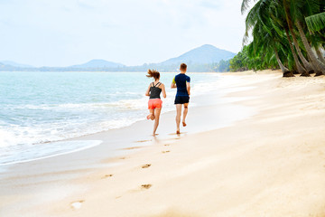 Healthy Lifestyle. Athletic Runner Couple Running On Beach, Training For Marathon. Sporty Fit People Jogging Near Sea ( Ocean ) During Outdoor Workout. Sports And Fitness. Exercising. Health Concept