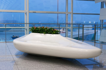 Futuristic design public white bench at an airport