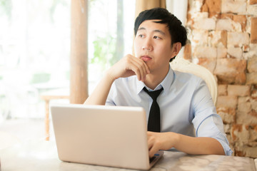 Young Asian casual businessman thinking while working in outdoor