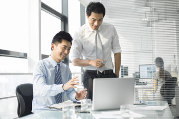Young businessmen talking in office