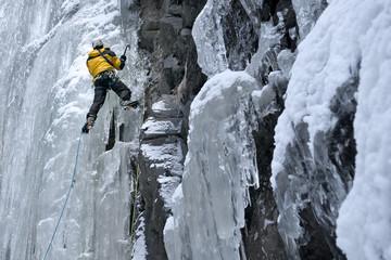 Bergsteiger klettert mit Eisgeräten und Steigeisen einen gefrorenen Wasserfall hinauf. Sicherung an Eisschrauben mit Doppelseiltechnik.
