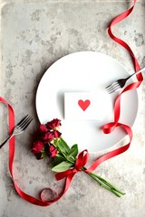 Red heart message card on the white dish with red rose bouquet