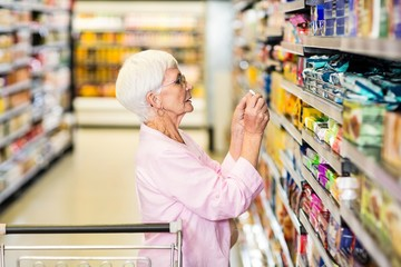 Senior woman taking a picture of product on shelf