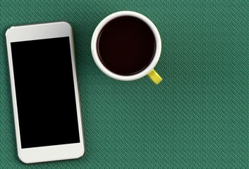Coffee cup with smart phone on green fabric table