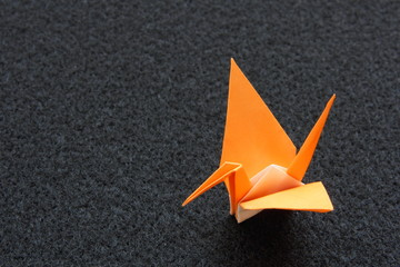 Orange paper crane on black felt mat