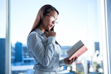 Concentrated businesswoman reading book