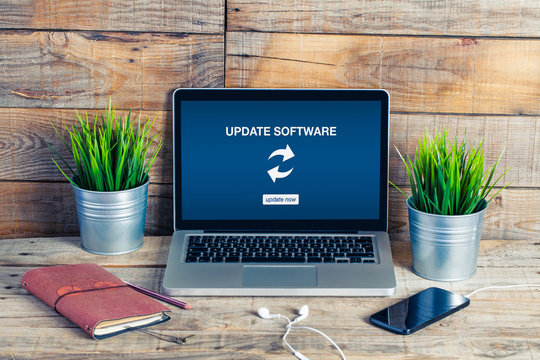 Update software notice in a laptop. Wooden desk office.