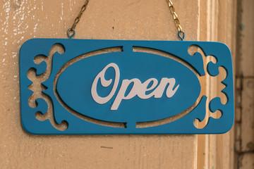 A sign hanging in the front door open.
