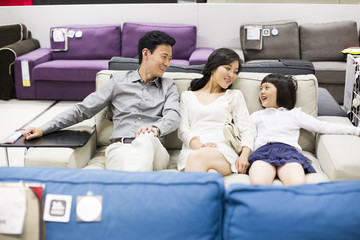 Happy family shopping for sofa in furniture shop