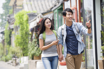 Young couple travelling in Beijing Hutong with smart phone