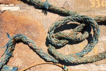 Weathered Nautical Rope on a Pier / Detail of weathered nautical rope, blue and orange, on the pier in the harbor