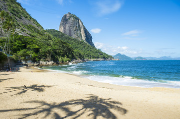 Praia Vermelha Red Beach quiet afternoon with view of Sugarloaf Mountain Pao de Acucar and palm tree shadows Rio de Janeiro Brazil