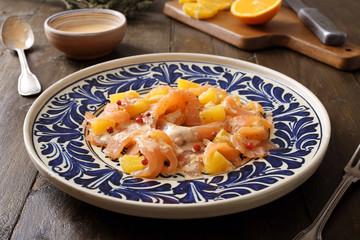 salmone affumicato insalata con arancia in piatto su sfondo rustico