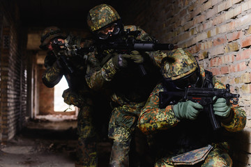SWAT team during a special operation/Team of three elite police marksmen in German uniform with weapon in building.